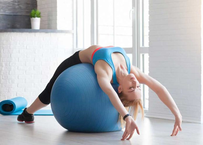 Fit sportswoman doing pilates with stability ball